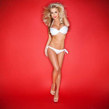 Blonde jeune femme en bikini blanc isolé sur fond rouge