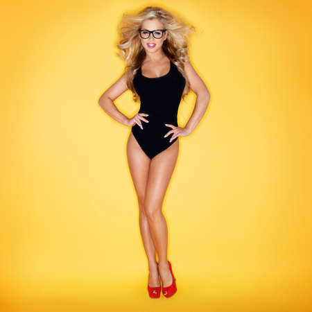 Blonde Woman In Swimsuit Wearing Eyeglasses On Yellow Background Stockfoto