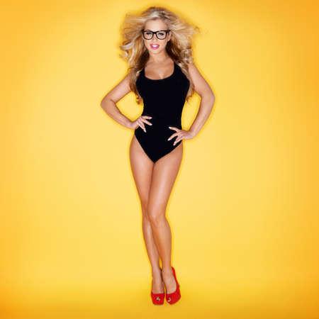 Blonde Woman In Swimsuit Wearing Eyeglasses On Yellow Background Foto de archivo