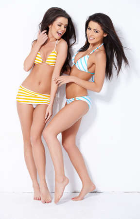 Happy ladies posing in swimsuits on white background photo