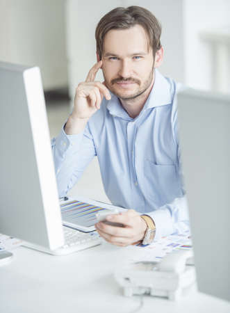Businessman sitting in front of computer monitors at the desk photo
