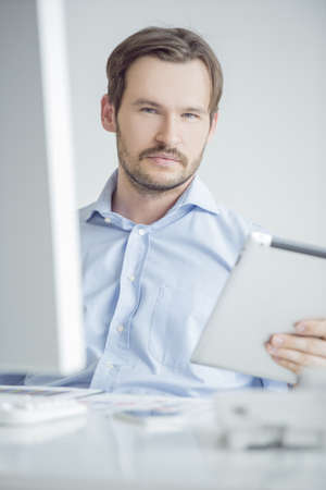 Attractive male sitting at his desk in the office photo