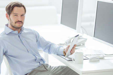 Handsome businessman sitting in front of monitors with his tablet photo