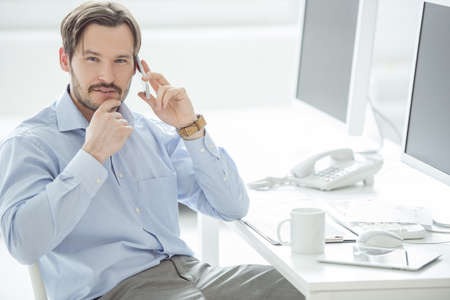 Close up of businessman talking mobile phone at the desk photo