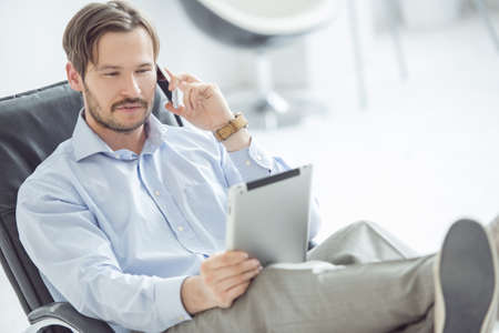 Relaxed businessman talking mobile phone at the desk photo