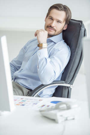 Handsome businessman sitting in chair in front of computer screen photo