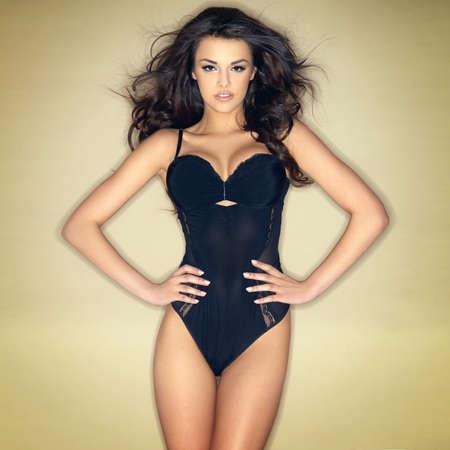 black lingerie: Sexy brunette girl posing in black lingerie isolated on green background