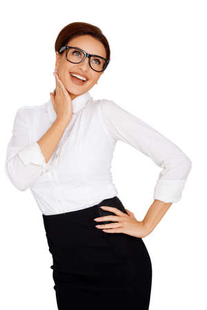 hands on hips: Laughing businesswoman in glasses standing with her hand on her hip looking upwards towards the sky  three quarter length studio portrait
