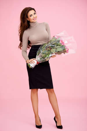 busty woman: Beautiful elegant stylish woman with a large bouquet of cellophane wrapped roses in her hand received as a gift for Valentines Day or her anniversary Stock Photo