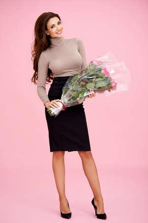 busty: Mooie elegante modieuze vrouw met een groot boeket van cellofaan verpakte rozen in haar hand als een geschenk voor Valentijnsdag of haar verjaardag