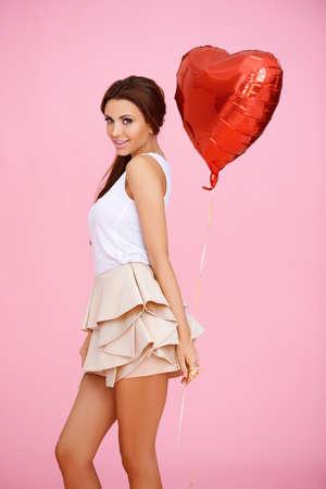 miniskirt: Cute brunette with red heart balloon on pink