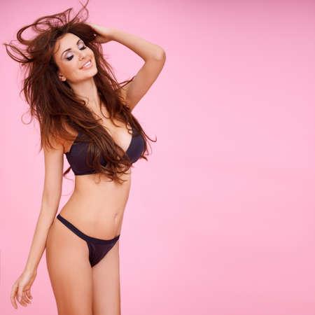 busty: Mujer de risa vivaz con el pelo largo Morena soplando en el viento en un sexy bikini negro sobre un fondo de color rosa de estudio