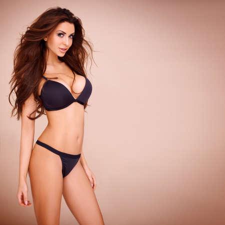 busty: Sexy pose van een donkerharige vrouw, gekleed in een zwarte bikini