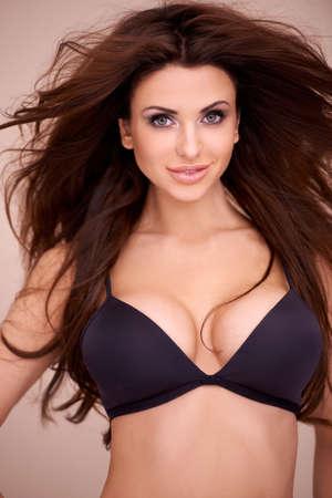 Haut du corps portrait d'une belle femme plantureuse aux longs sauvage modélisation des cheveux bruns, un bikini