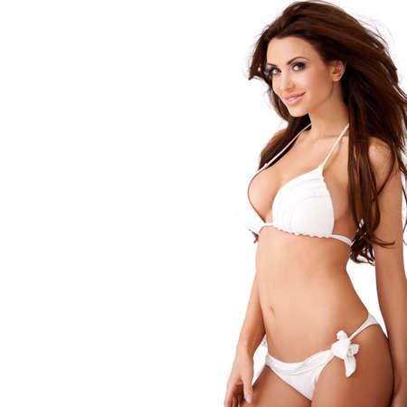 Sourire sexy jeune femme brune avec un beau chiffre posant dans un bikini blanc trois quarts isolé portrait en studio
