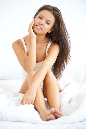 Happy and Beautiful woman sitting on white bed Stock Photo - 21639096
