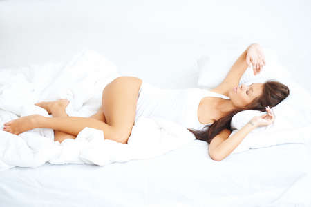 Young sexy girl lying on white bed with eyes closed photo