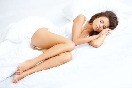 Young sexy girl lying on white bed with eyes closed Stock Photo - 21639120