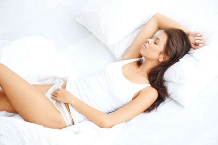 Young sexy girl lying on white bed with eyes closed Stock Photo - 21639122