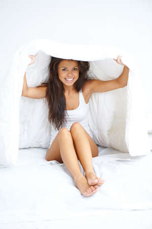 coverlet: Young woman hiding under the bedclothes peeking out from under the duvet and smiling at the camera Stock Photo