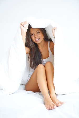 Young woman hiding under the bedclothes peeking out from under the duvet and smiling at the camera Stock Photo - 21639134