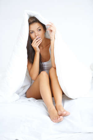 Young brunette woman hiding under coverlet Stock Photo - 21639135