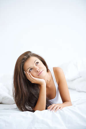 Young sweet lady lying on white bed and dreaming Stock Photo - 21639142