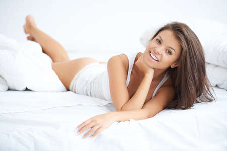 Smiling beautiful woman relaxing in bed enjoying a lazy day and looking at the camera with a radiant smile photo