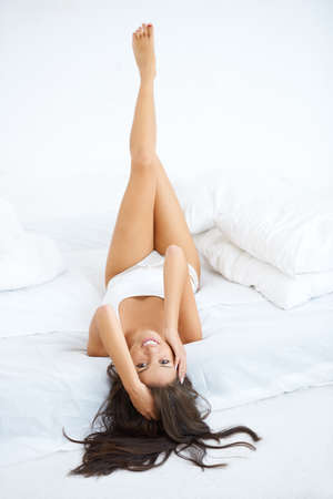 High angle view of a pretty young  woman lying on her back on the bed in her sleepwear with her long bare legs raised in the air photo