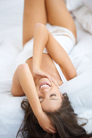 Happy and relaxed young woman having fun on bed photo
