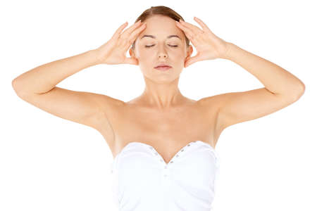 unwind: Woman meditating  standing with her hands to the sides of her face  eyes closed and a serene expression as she takes a moment to relax and unwind