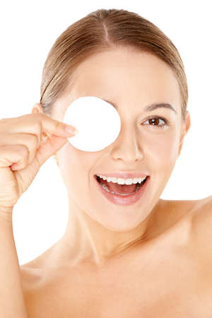 eye pad: Laughing beautiful young woman holding a round white cotton pad to her eye  close up portrait