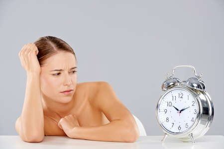 consternation: Beautiful young woman looking at a large silver retro alarm clock with bells in consternation as though waiting for it to ring