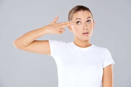 kill: Woman making a handgun gesture with her hand pointing her fingers at her temple while frowning at the camera Stock Photo