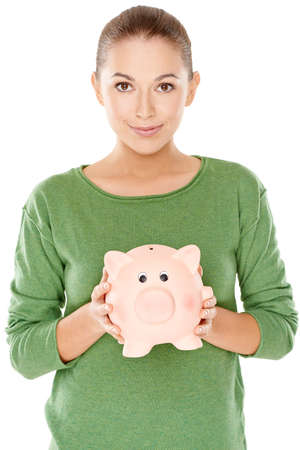 thrift box: Beautiful young woman with her piggy bank as she holds it in her hands