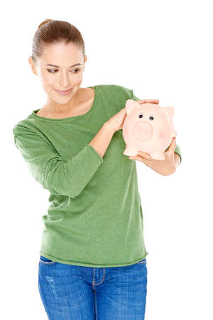 thrift box: Beautiful young woman giving her large pink piggy bank a speculative look as she holds it in her hands