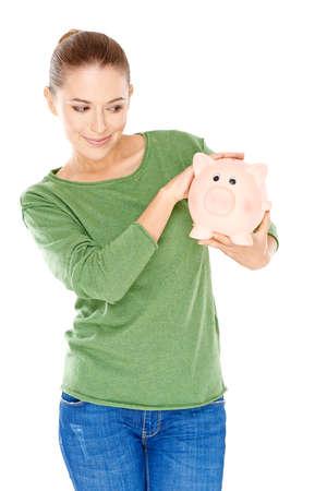 quizzical: Joven y bella mujer que da a su gran hucha rosa una mirada especulativa como ella sostiene en sus manos