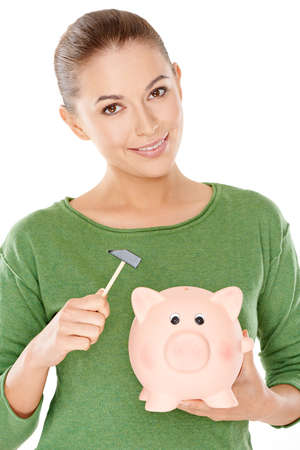 thrift box: Woman contemplating opening her piggy bank standing holding it in one hand and a small mallet in the other as she smiles at the camera Stock Photo