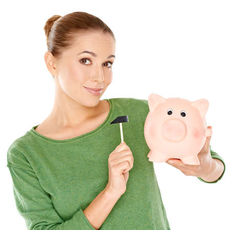 thrift box: Pretty smiling young woman testing her piggy bank with a small mallet either to see how full it is or in contemplation of raiding it for cash  isolated on white