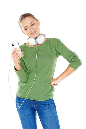 downloaded: Beautiful young woman with headphones slung around her neck smiling at her choice of downloaded music on her storage device  isolated on white