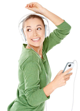 listening device: Happy woman dancing to her music which she is listening to on headphones while holding the music storage device in her hand Stock Photo
