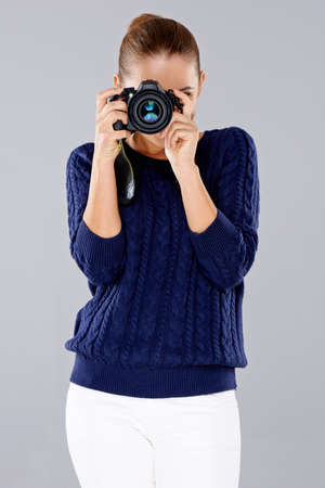 dslr camera: Stylish young woman photographer taking a photograph on a professional dslr camera pointing the lens directly at the viewer Stock Photo