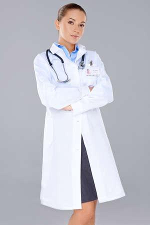 bata de laboratorio: Hermosa mujer médico confía en pie en una bata de laboratorio blanco mirando a la cámara con los brazos cruzados sobre fondo gris Foto de archivo
