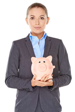 nestegg: Attractive young businesswoman holding a piggy bank in her hands standing looking directly at the camera with a serious earnest expression  isolated on white Stock Photo