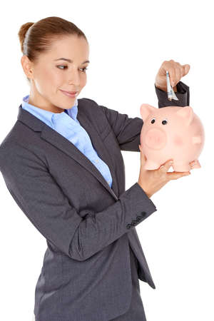 nestegg: Stylish beautiful successful businesswoman with a piggy bank in her hand about to deposit a bank note into the slot to save towards her retirement or a personal goal Stock Photo