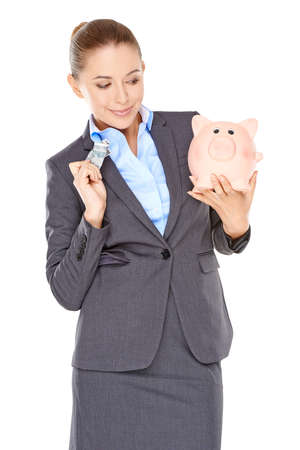 nestegg: Woman deciding whether to spend or save holding a dollar bill in one hand and her piggy bank in the other with a wry expression  isolated on white