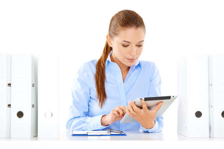 overwrought: Dedicated young businesswoman hard at work at her desk on a tablet computer surrounded by large office binders Stock Photo
