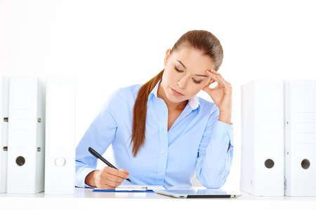 overwrought: Efficient businesswoman working at her desk sitting writing notes from a tablet computer surrounded by neat rows of office files