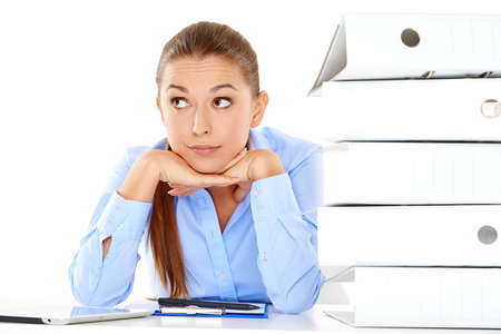 overwrought: Overworked stressed young businesswoman staring at the camera with her head on her hands alongside a tall stack of office files with paperwork Stock Photo