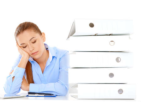 overwrought: Tired young businesswoman taking a nap at her desk during her lunch break resting her head on her hand alongside a tall stack of office files